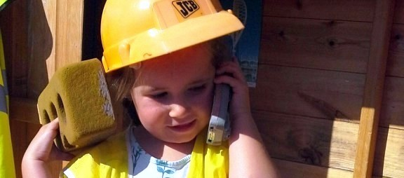 toddler girl wearing a dress-up construction helmet and high vis holding a toy phone to her ear